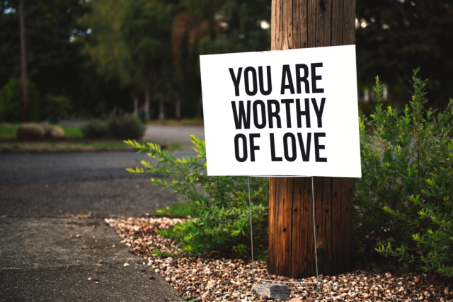 "A white sign with black text reading ""You are worthy of love"" stands next to a wooden pole off a forest trail."