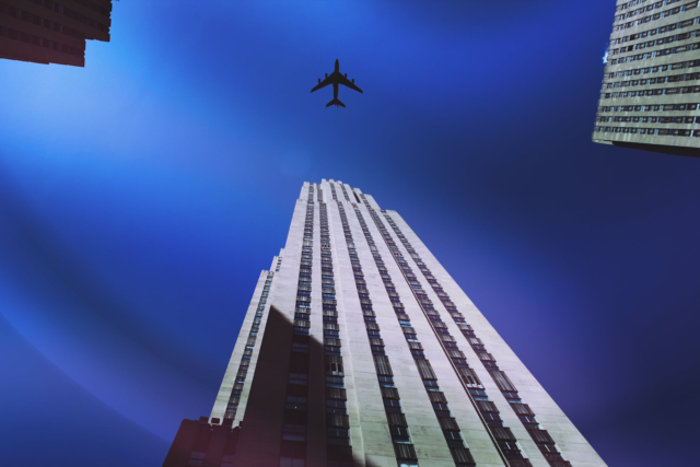 A jet flying over the Empire State Building in New York City.